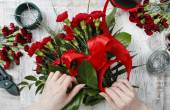 Florist at work. Woman making bouquet of red carnations — Stock Photo
