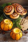 Orange pomander balls with candles and cinnamon rolls — Stock Photo