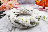 White wicker wreath decorated with tiny daisies — Stock Photo