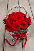 Bouquet of red roses in wicker basket — Stock Photo