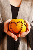 Woman holding orange pomander ball — Stock Photo