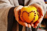 Woman holding orange pomander ball — Stock Photo