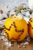 Orange pomander ball with candle decorated with cloves — Photo