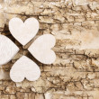 Shamrock (clover) made of wooden hearts on bark background. — Stock Photo #61103733