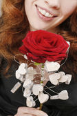 Woman holding red rose decorated with wooden hearts — Stock Photo