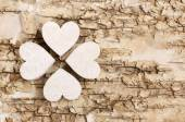Shamrock (clover) made of wooden hearts on bark background. — Stock Photo