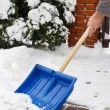 Man removing snow from the sidewalk after snowstorm — Stock Photo #74606665