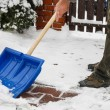 Man removing snow from the sidewalk after snowstorm — Stock Photo #74606669
