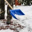Man removing snow from the sidewalk after snowstorm — Stock Photo #74606673