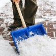 Man removing snow from the sidewalk after snowstorm — Stock Photo #74606677