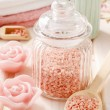 Glass jar of pink sea salt on white wooden table — Stock Photo #74608575