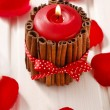 Red scented candle decorated with cinnamon sticks. Rose petals a — Stock Photo #74608765