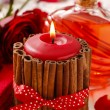 Red scented candle decorated with cinnamon sticks. Rose petals — Stock Photo #74608781