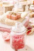 Стеклянная банка розовый морской соли на белый деревянный стол — Стоковое фото