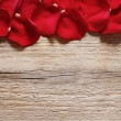 Red rose petals on wooden background — Stock Photo #76379667