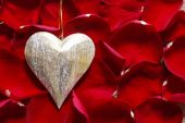 Golden heart on red rose petals — Stock Photo
