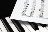 Music paper sheet lying on th piano keys — Stock Photo