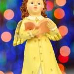 Christmas decoration, figure of little angel singing carols against bokeh background — Stock Photo #57841333