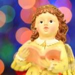 Christmas decoration, figure of little angel singing carols against bokeh background — Stock Photo #57841341