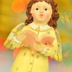 Christmas decoration, figure of little angel singing carols against bokeh background — Stock Photo #57841347