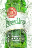 Pilsner Urquell pale lager beer in splashed water — Stock Photo