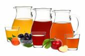 Apple, plum and peach juice in glasses and decanters — Stock Photo