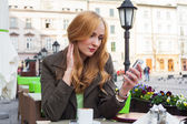 Elegant woman using smartphone in a cafe — Foto Stock