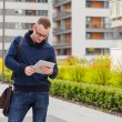 Young man with tablet pc on street — Stock Photo #55761319