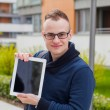 Young man with tablet pc on street — Stock Photo #55761491
