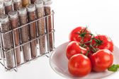 Red tomatoes and ground spices in bottles — Stock Photo
