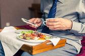 Man using mobile phone during breakfast — Foto Stock