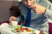 Businessman eating breakfast at home — Stock Photo