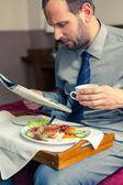 Businessman reading newspaper during breakfast — Stock Photo