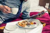 Businessman working on tablet during breakfast — Stock Photo