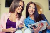 Two cheerful friends looking at tablet pc. — Stock Photo