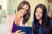 Two cheerful friends looking tablet pc. — Zdjęcie stockowe