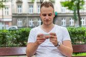 Handsome man in park using smartphone. — Foto Stock