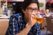 Asian man drinking beer in a bar — Stock Photo