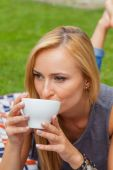 Woman lying in park and drinking coffee — Stock Photo