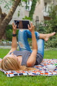 Woman using tablet pc in park — Stock Photo