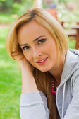 Smiling blonde woman in park — Stock Photo