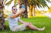 Tourist  under palm  with mobile phone — Stock Photo