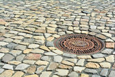 Manhole cover and cobblestones — Stock Photo