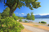 Idyllic waterside promenade, lake tegersee — Stock Photo