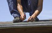 Gardener repairing roof of summer garden house — Stock Photo