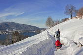 Father pulling son with a sledge, winter hiking trail, tegernsee — Stock Photo