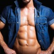 Muscular and sexy young man in jeans shirt — Stock Photo #68381393