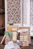 Old books heap and candle in vintage interior decoration — Stock Photo
