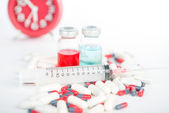 Injection syringe and medicine on red clock background — Stock Photo