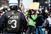 Detail of the Back of a Police Facing protesters. — Stock Photo